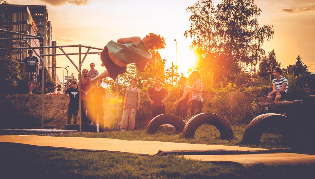 junger Mann beim einer Drehung in der Luft, im Hinergrund 10 Zuschauer:innne und der Sonnenuntergang