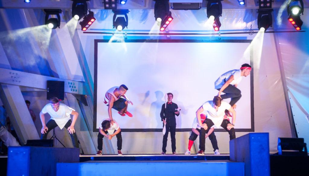 junge Menschen bewegen sich geschickt über die Bühne im Hintergrund eine jonglierende Person