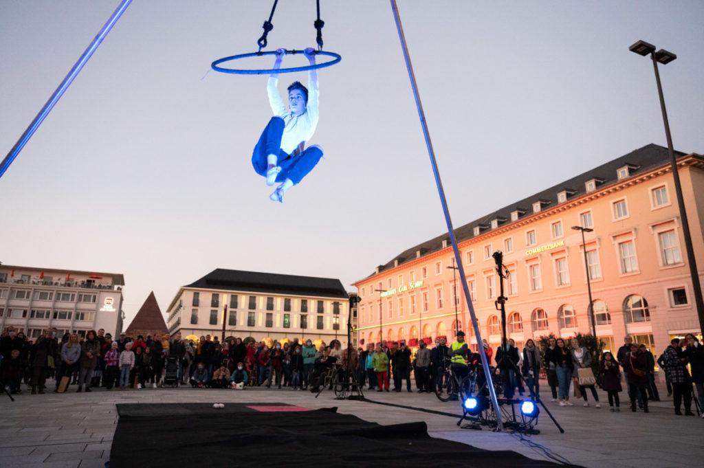 junger Mann hängt an einem Ring im Hintergrund der Karlsruher Marktplatz